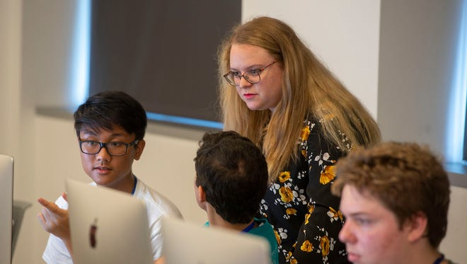 Megan Morton, student assistant for the GenCyber Camp combination camps for high school students and middle and high school teachers helps students in a class on Thursday, July 12, 2018.