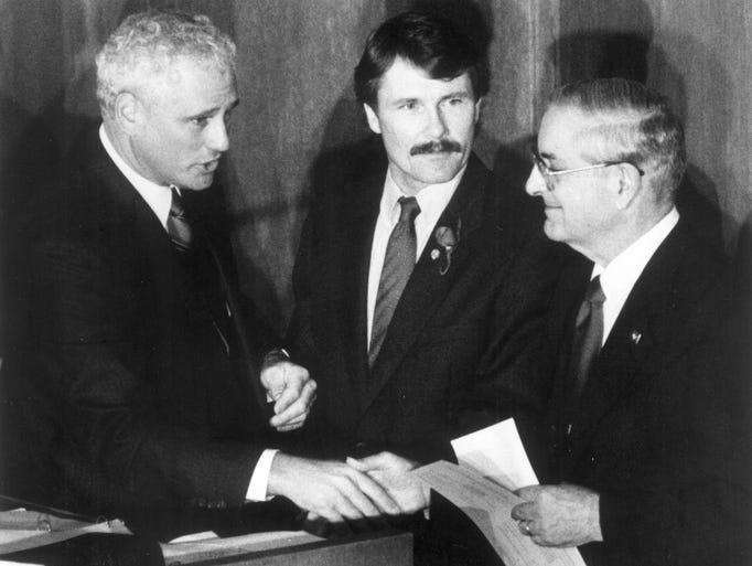 New Gov. Neil Goldschmidt shakes former Gov. Atiyeh's hand after Atiyeh made his farewell speech in 1987. Senate President John Kitzhaber looks on.