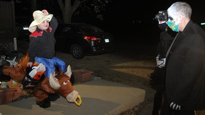 Elias Beasley, left, is all smiles after receiving candy from Todd McKenna, right, and Fiona Whelan during Trick or Treat in Reverse on Saturday at his home in Freeport.