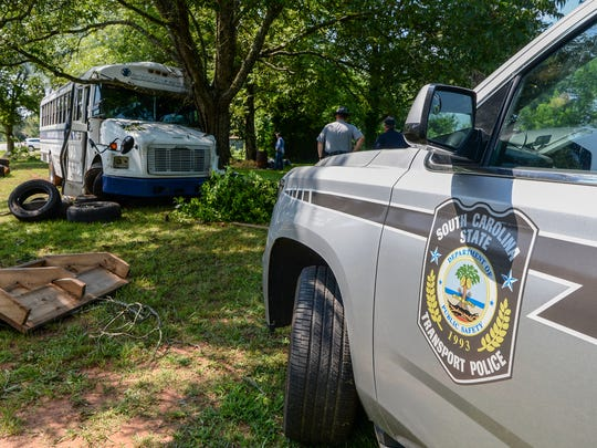 A State Transport Police vehicle is parked near a church bus from Oakwood Baptist Church, which crashed at 1611 Pearman Dairy Road in Anderson on Tuesday.