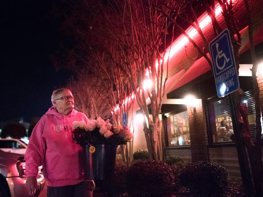 Brenda Scott, of Lexington, approaches Redbone's Grill and Bar with her bucket of roses Friday, Jan. 26, 2018, during her weekly bar rounds in Jackson. Each Friday and Saturday, Scott frequents The Office Lounge, Redbone's Bar and Grill, Mulligan's, the Tap Bar and Grill and Cody's Saloon Hall.