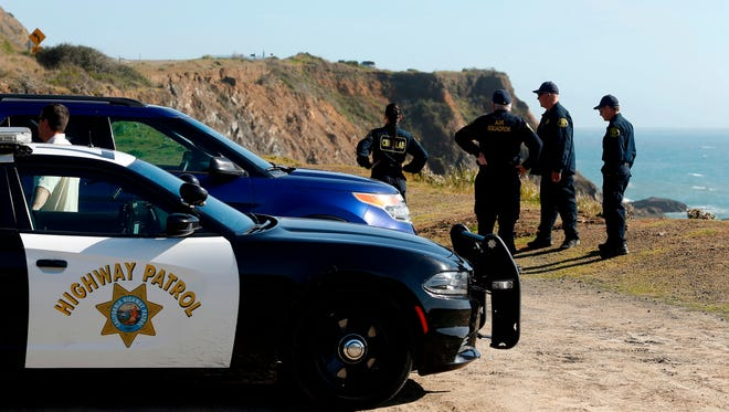 FILE - In this March 28, 2018, file photo, California Highway Patrol officers and deputy sheriffs from Mendocino and Alameda counties gather after a search for three missing children at the site where the bodies of Jennifer and Sarah Hart and three of their adopted children were recovered two days earlier, after the family's SUV plunged over a cliff at a pullout on the Pacific Coast Highway near Westport, Calif. Three of the children, Devonte Hart, 15, Hannah Hart, 16, and Sierra Hart, 12, have not been found. Authorities say a woman who drove off California cliff last month in an SUV carrying her wife and children was drunk. California Patrol Capt. Bruce Carpenter said Friday, April 13, 2018, that toxicology tests found Jennifer Hart had an alcohol level of .102. California drivers are considered drunk with a level of 0.08 or higher. Authorities don't know who was at the wheel at the time of the accident.