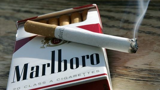 A Marlboro cigarette burns as it sits on a pack of Marlboro cigarettes.