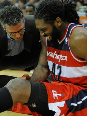 Wizards power forward Nene holds his knee after a sprain Sunday.
