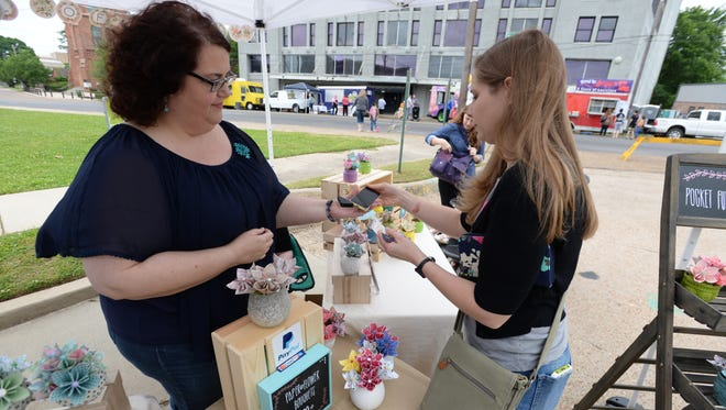 Karen Hanchey of Ruston pays Becky Snodgrass while shopping at the Pocket Full of Posies booth at Makers Fair.