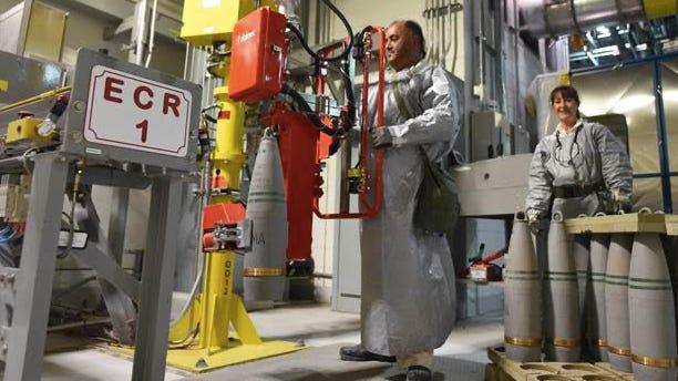 A Pueblo Chemical Agent-Destruction Pilot Plant ordnance technician uses a lift assist to transfer a 155 mm projectile onto a conveyor belt prior to destruction in fall 2019.