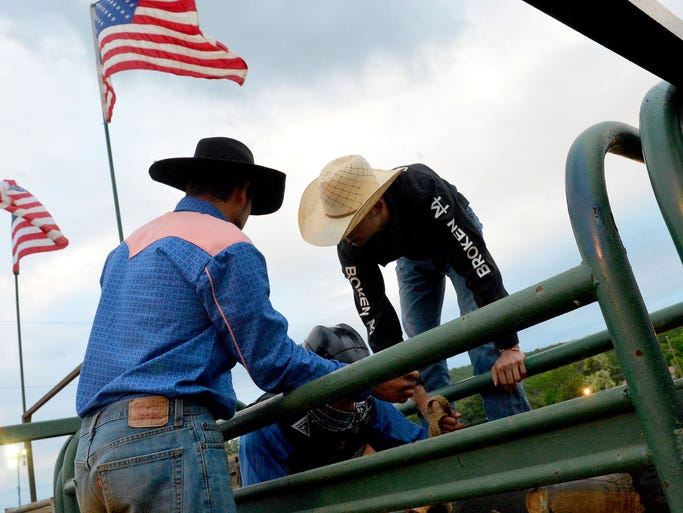 Bull rider Max Miller (right) of Staunton helps a rider already on a bull in a starting chute with getting ready before a ride during the Gordonsville Bull Riding Rodeo at Oakland Heights Farm in Gordonsville on Saturday, May 10, 2014.