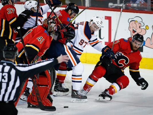 Edmonton Oilers center Connor McDavid (97) scuffles with Calgary Flames defenseman TJ Brodie (7) as goaltender Mike Smith (41) looks on during the third period of an NHL hockey game, Tuesday, March 13, 2018, in Calgary, Alberta. Calgary defeated Edmonton 1-0. (Jeff McIntosh/The Canadian Press via AP)