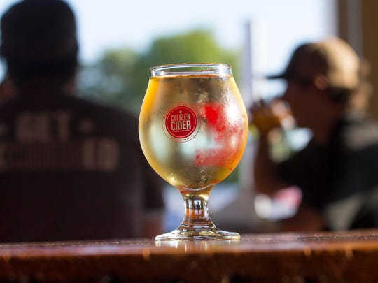 Patrons provide a backdrop for a cold glass of hard cider at the Citizen Cider tasting room on Pine Street, in Burlington, Vt.,Tuesday, August 27, 2014.