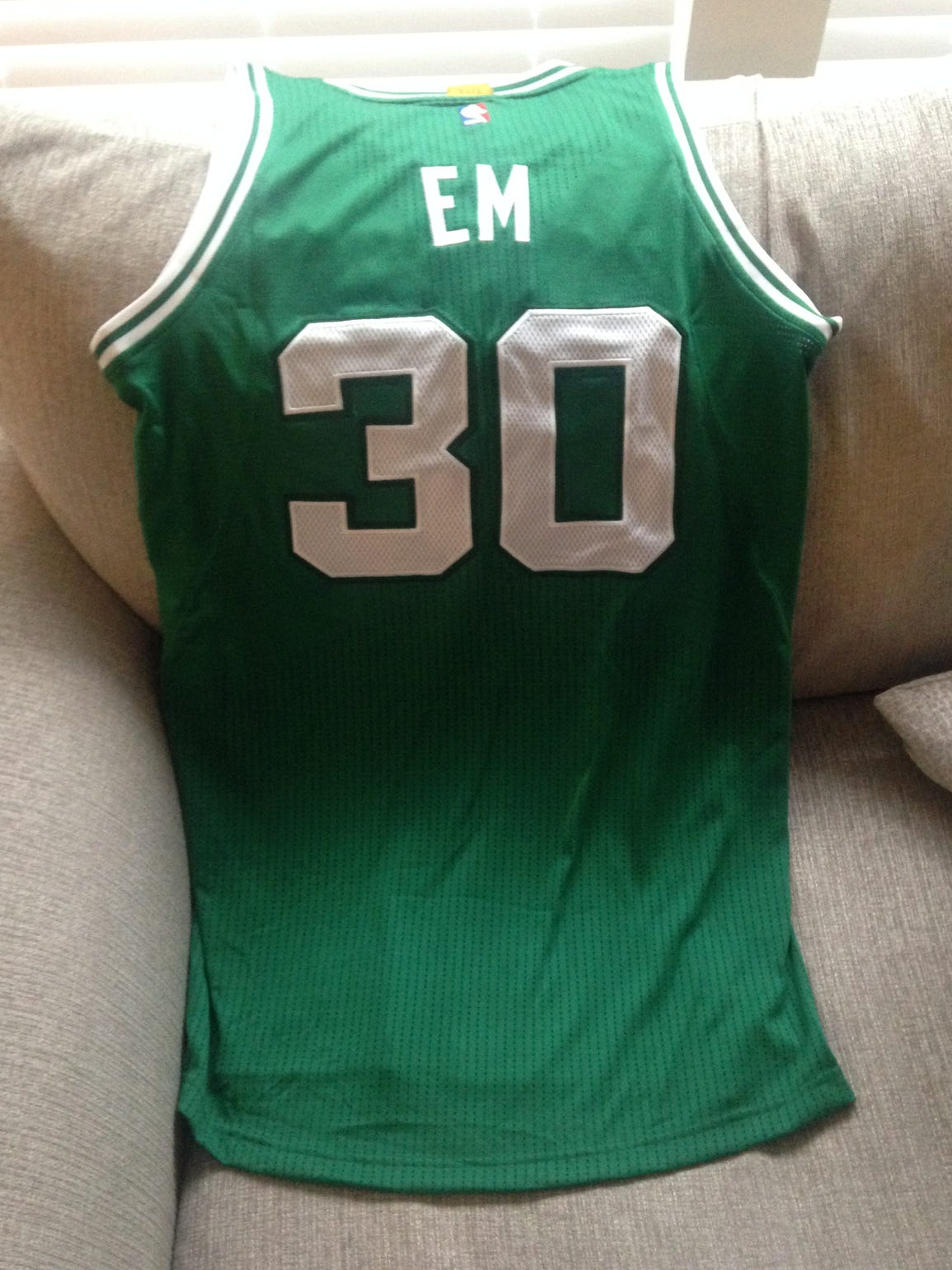 A Celtics green jersey with Baby Em's name and his