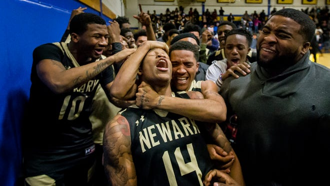 Newark's Michael Drumgo-Sharpe (No. 14) is mobbed by teammates after hitting a game-winning shot as time expired in the fourth quarter of Newark's 52-51 win over A.I. du Pont High School in Greenville on Tuesday evening.