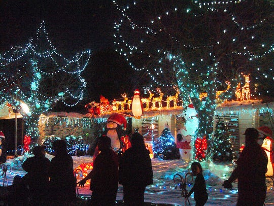 Visitors walk through the decorated homes in and around
