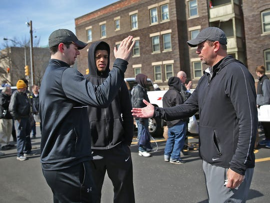 Brock Blackwell, left, and Jefty Sultzer talk with Todd Leary as Indiana Faith AAU team members serve the community last month.
