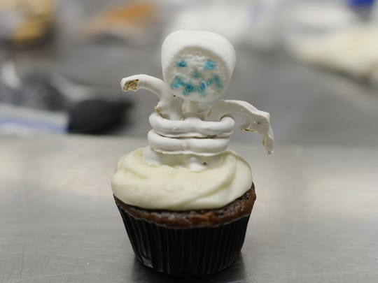 Yogurt covered pretzels form the rib cage and arms for this skeleton cupcake.