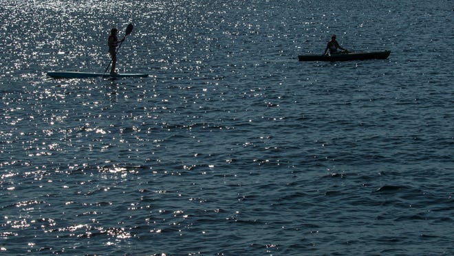 In this file photo, a paddleboarder and a kayaker row their way along the Cape Coral Yacht Club beach.