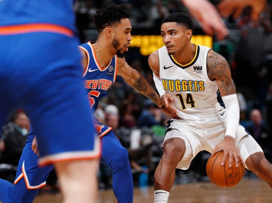 New York Knicks guard Courtney Lee, left, stops Denver Nuggets guard Gary Harris as he drives to the basket in the second half of an NBA basketball game Thursday, Jan. 25, 2018, in Denver. (AP Photo/David Zalubowski)