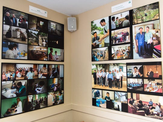 Photographs on display of workers from the organization Christian Friends of North Korea working with North Koreans at the organization's office in Black Mountain.