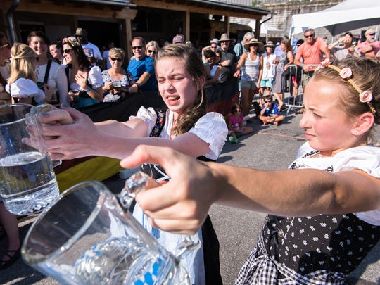 Cassidy Bowen, 12, and Sammi Hascher, also 12, of Hendersonville, participate in the children's stein hoisting competition at the 7th annual Southern Appalachian Brewery Oktoberfest in Hendersonville, Saturday, September 23, 2017.