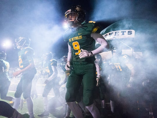 Reynolds' Bryan Patton runs out of their tunnel with the his team at the start of their game against Southwest Guilford Friday, November 17, 2017.