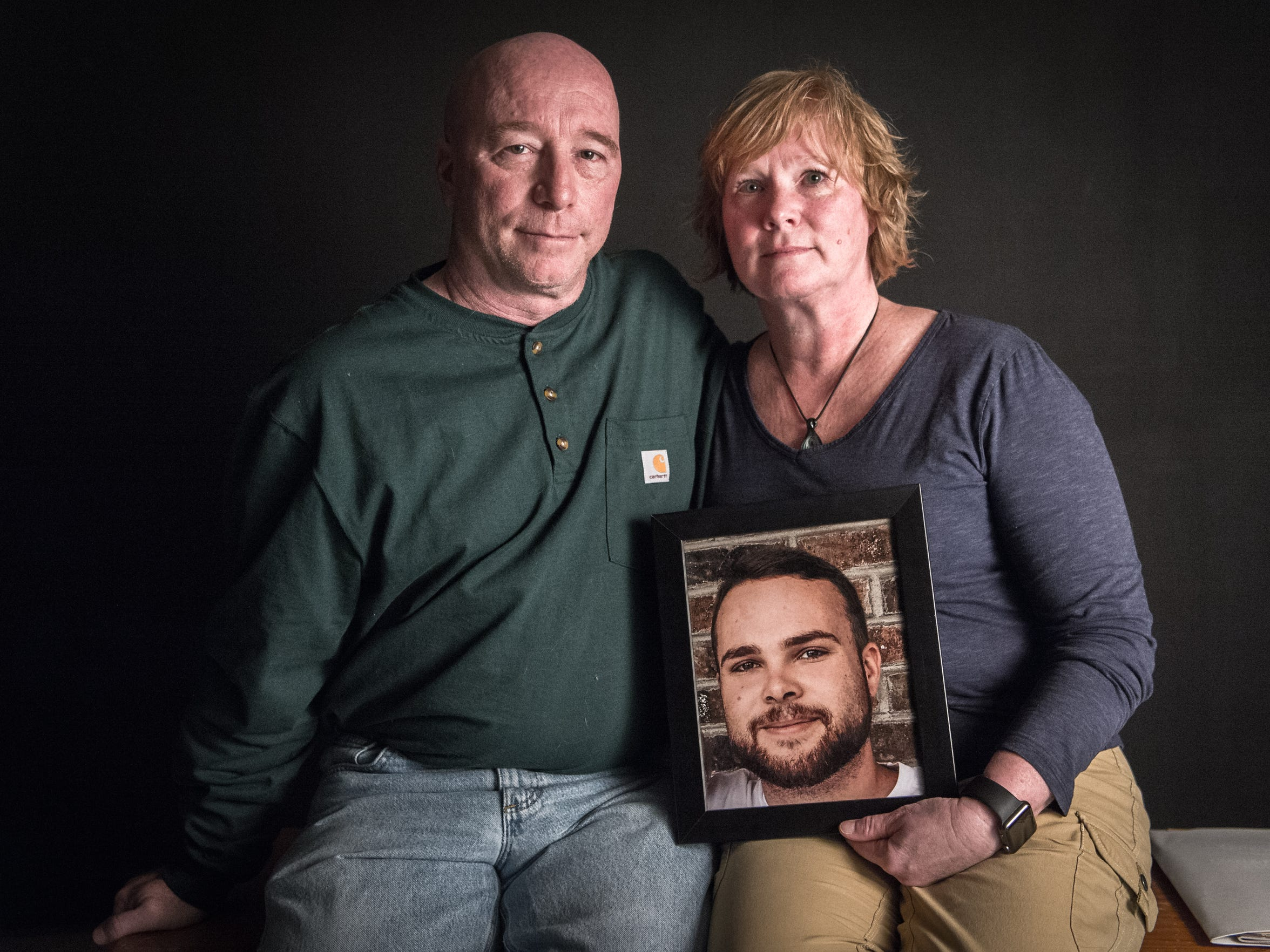 Rob and Sherry Abbot hold a portrait of their son Seth