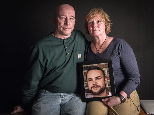 Rob and Sherry Abbot hold a portrait of their son Seth Abbot who died of an opioid overdose in March of 2017 at the age 24.