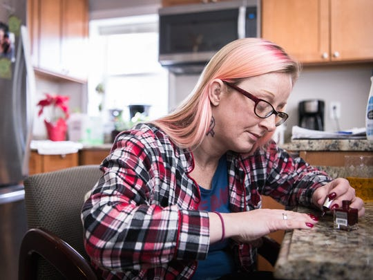 Hope Bishop paints her nails in her apartment in Asheville before her drug court graduation ceremony at the Buncombe County Courthouse, Friday, February 2, 2018.