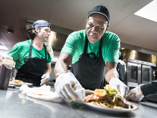 William Raines, a student in Green Opportunities' Kitchen Ready program plates food during their showcase dinner at the Southside Kitchen in Asheville Thursday, February 22, 2018.