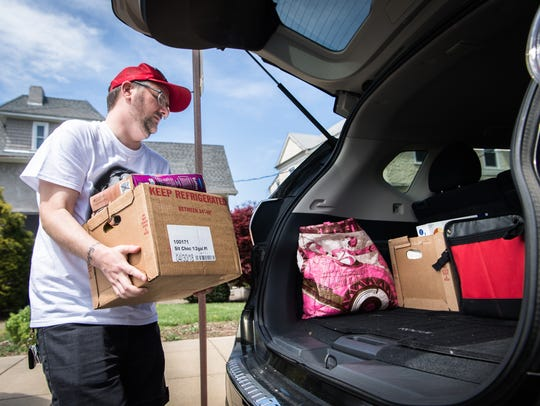 Stephen Wiseman, of Asheville, helps load a car with