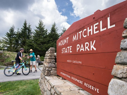 A cyclist stops at the entrance to Mt. Mitchell State