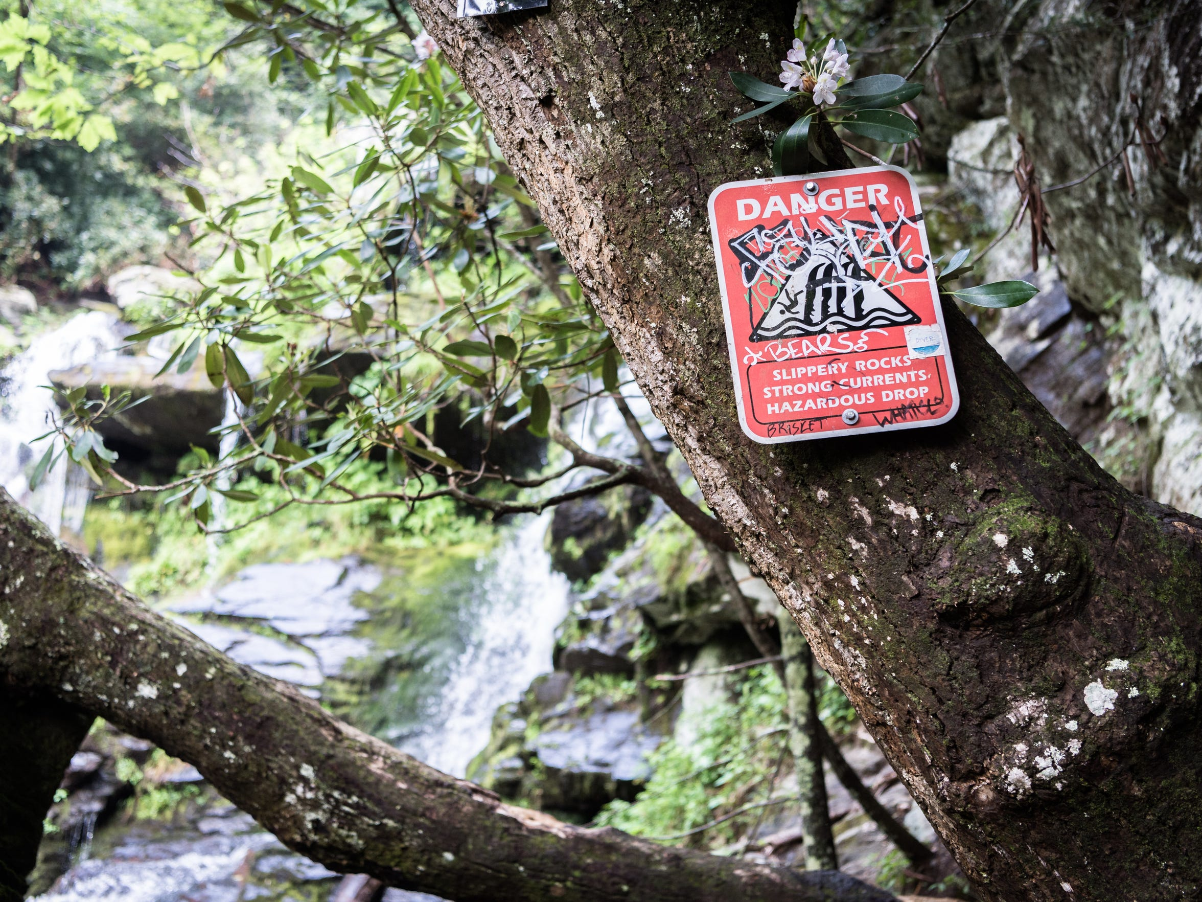 Signage warning visitors to Catabwa Falls in the Pisgah National Forest in Old Fort of the hazards of climbing around the waterfalls.