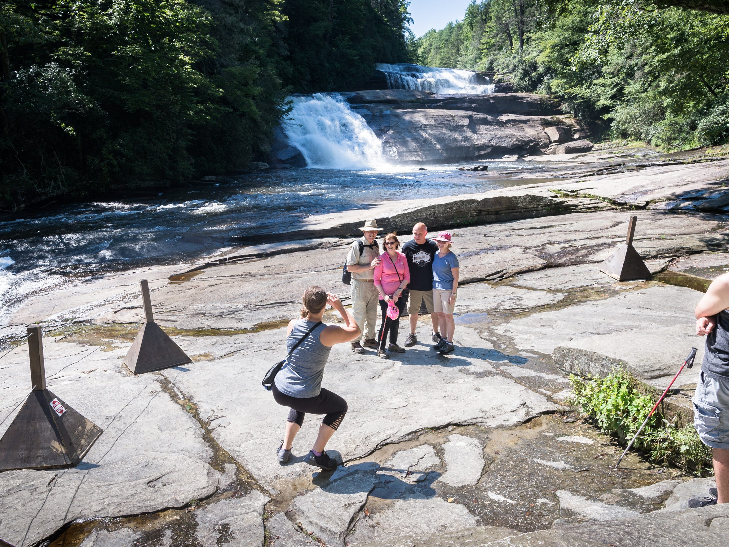Visitors to Triple Falls in DuPont State Recreational Forest, view the falls from the roped-in viewing area at the base of the falls Thursday, July 26, 2018.