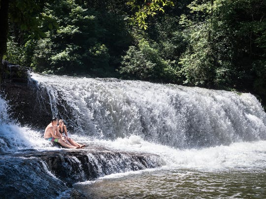 A couple sits on a ledge at Hooker Falls in DuPont