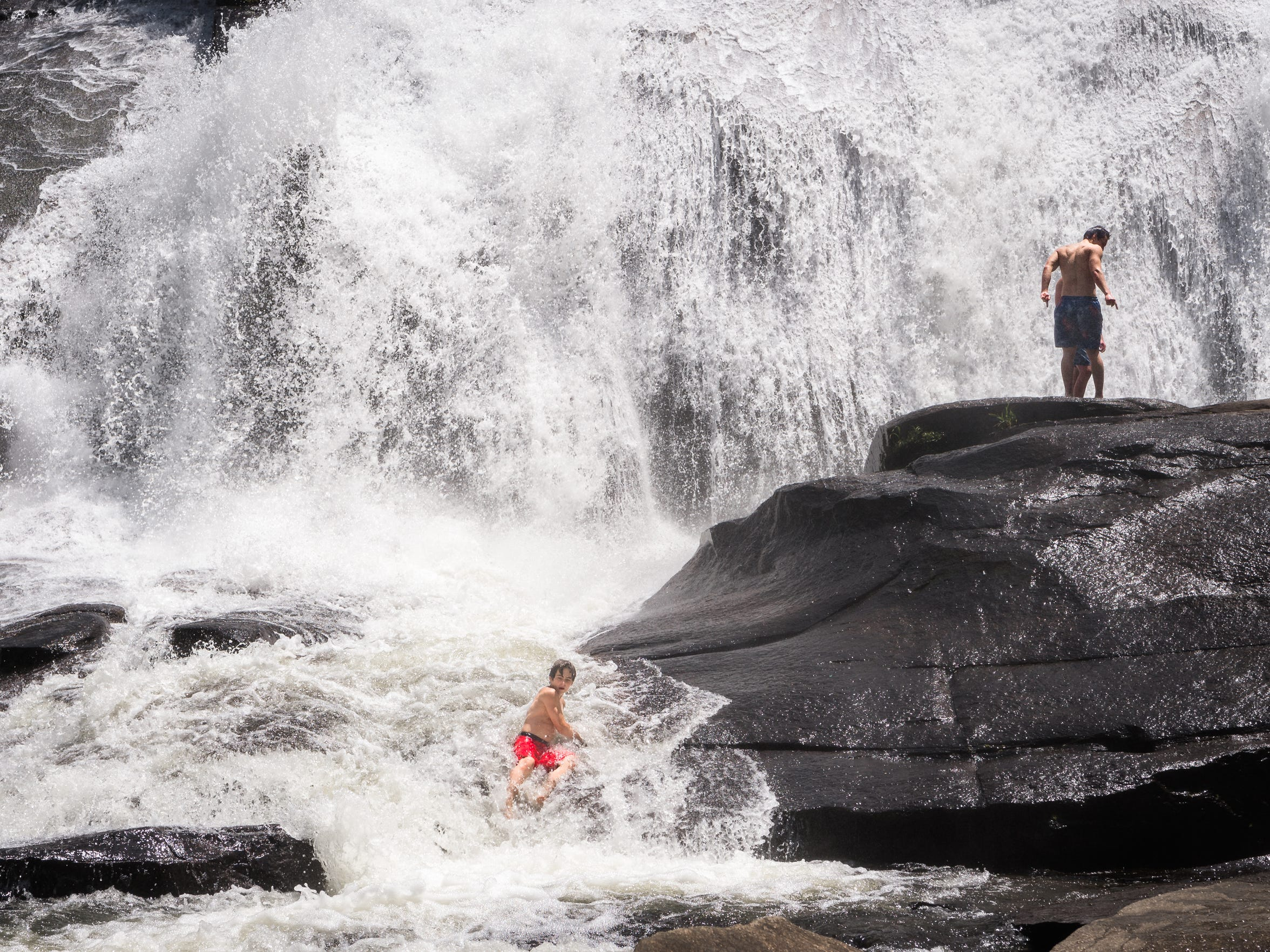 A young visitor to DuPont State Recreational Forest slides down rocks in front of High Falls Thursday, July 26, 2018.
