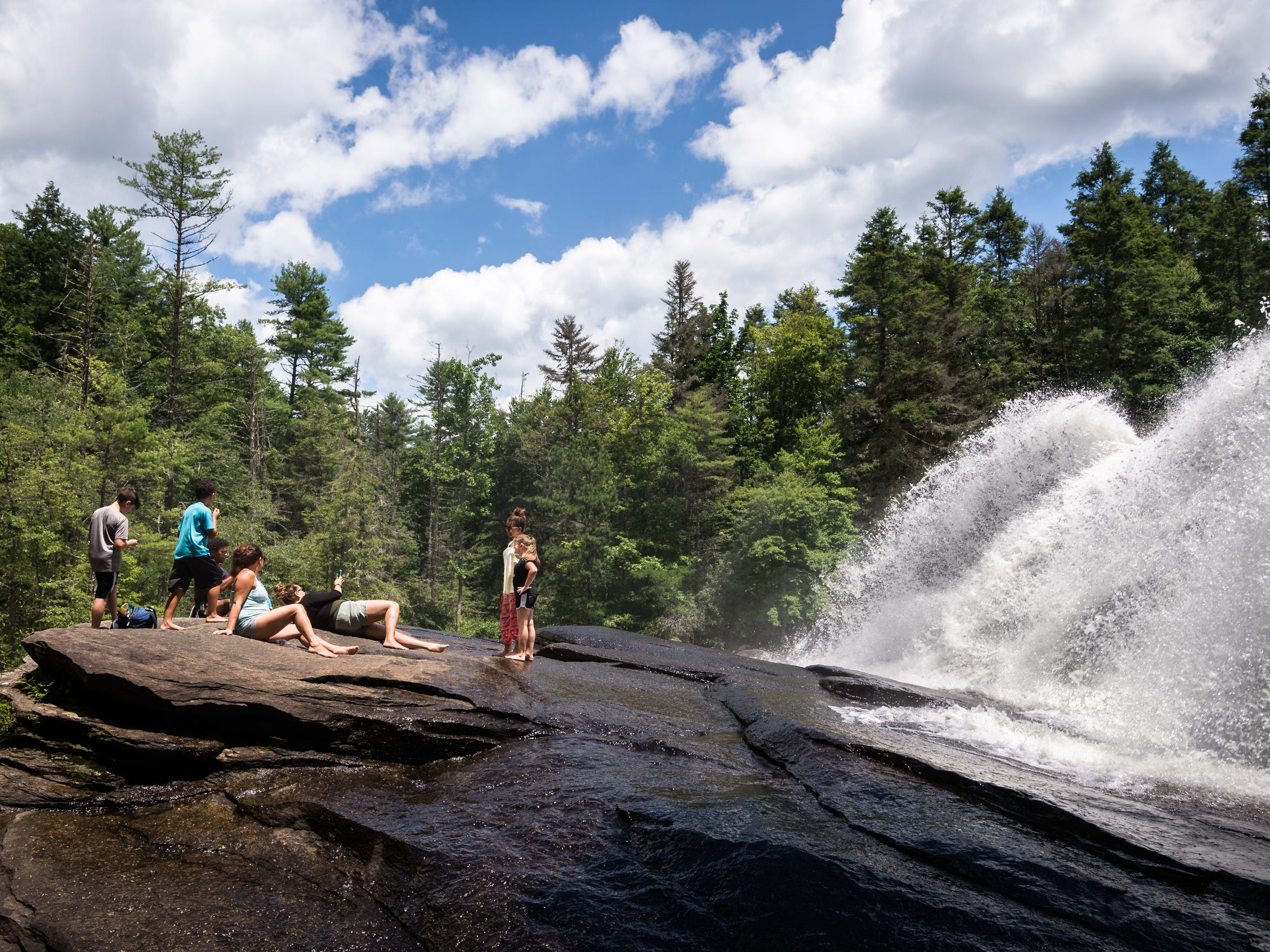 Visitors to DuPont State Recreational Forest lie on boulders in front of High Falls Thursday, July 26, 2018.