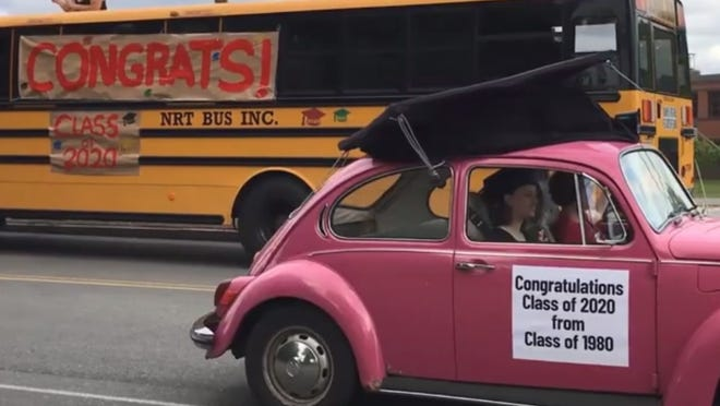Heidi Parisi, who graduated with the Masconomet Class of 1980, put a giant mortarboard on the top of her pink Volkswagen Beetle for the rolling tribute to the Masco Class of 2020, which took place Friday, May 29, on what would have been graduation day. Here, Parisi passes a school bus parked in front of Masconomet on Endicott Road in Boxford.