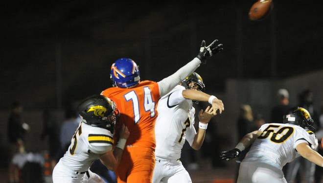 Newbury Park High quarterback Cameron Rising throws a pass before Cameron Kohler, 74, can reach him during Friday night's game. Rising led the Panthers to a comeback win over the Warriors.