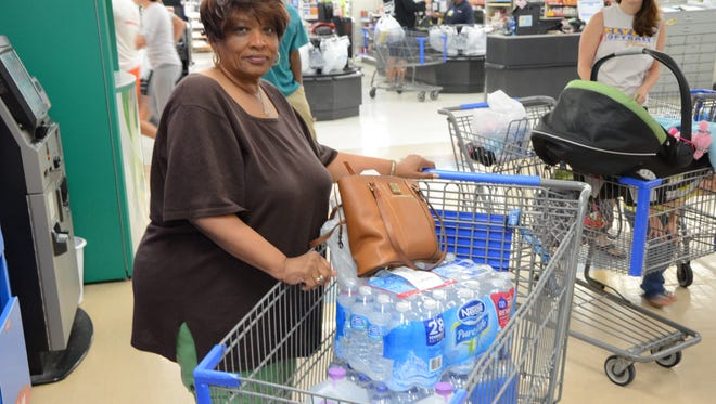 Lilli Carter, of Slyvania, stands next to her shopping cart of drinking water at the Fremont Wal-Mart Saturday. Carter's neice purchased the water earlier in the morning so her aunt could pick it up and have water for the weekend after residents were urged not to consume Toledo water. Rich McGowan/News-Messenger.