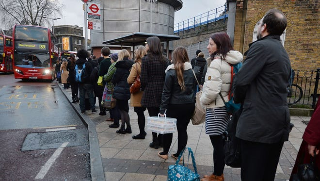 Commuters queue for buses at London's Waterloo station in central London, on Feb. 5, 2014.