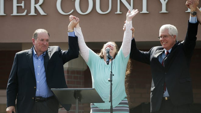 Rowan County, Ky., court clerk Kim Davis holds her hands in the air with her attorney, Mat Staver, right, and Republican presidential candidate Mike Huckabee in front of the Carter County Detention Center on Sept. 8, 2015, in Grayson, Ky.