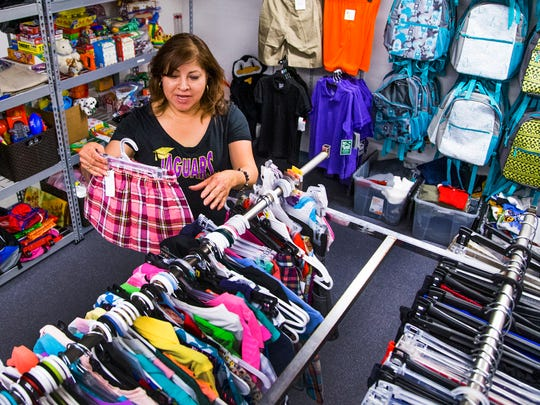 """Jefferson Elementary School in Mesa was recently designated an """"A+ School of Excellence."""" Chris Hernandez, secretary to the principal, shows off some of the clothing that children can receive free from the on-campus """"Boutique,"""" on April 21, 2017."""