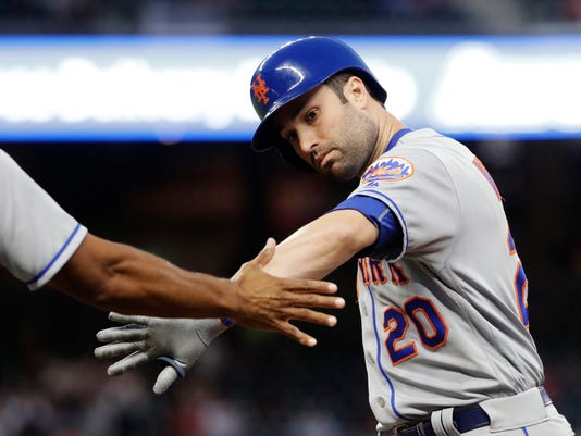 New York Mets' Neil Walker, right, greets first base coach Tom Goodwin after hitting a single to score teammate Asdrubal Cabrera in the fourth inning of a baseball game against the Atlanta Braves in Atlanta, Monday, May 1, 2017. (AP Photo/David Goldman)