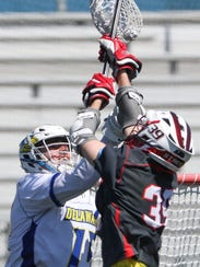 Delaware goalkeeper Matt DeLuca (left) grabs a rebound out of the air in front of Fairfield's Charlie Curran in Delaware's 11-10 win in their CAA season opener at Delaware Stadium.