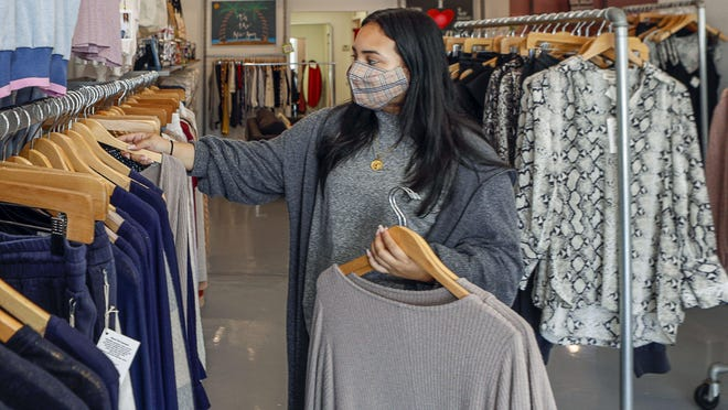 Sales assistant Xiara Del Valle hangs up Project Social cardigans inside Rapunzel's Closet, which will close next month after 18 years on the island.