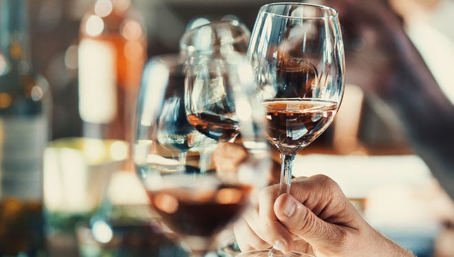 Closeup of group of unrecognizable people tasting different types of wines at a winery. Shallow focus, hands and glasses in the frame.