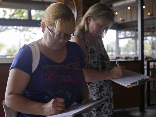 Terri Barkley (left) and Rochelle Kiggins sign a petition