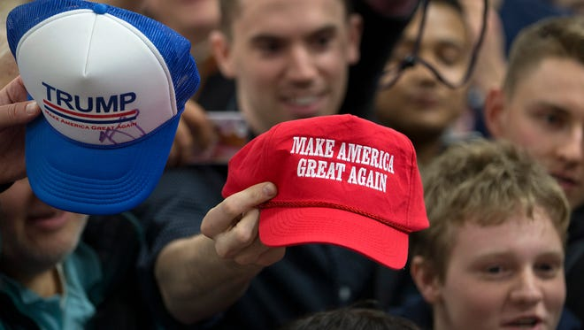Supporters hold out their hats to get them autographed by Republican presidential candidate Donald Trump at a rally Sunday, Jan. 31, 2016, in Council Bluffs, Iowa. (AP Photo/Jae C. Hong)
