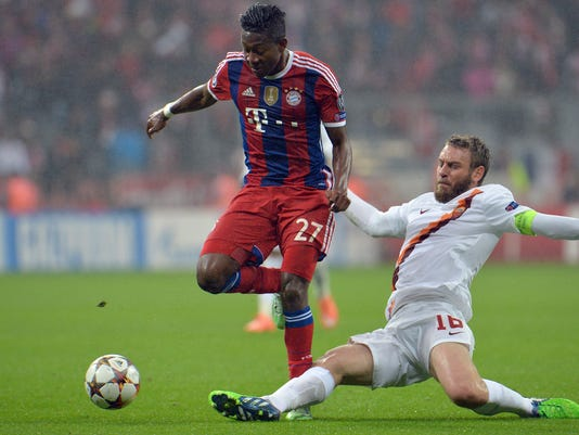 Bayern's David Alaba, left, and Roma's Daniele De Rossi  challenge for the ball during the Champions League group E soccer match between Bayern Munich and Roma in Munich, Germany, on Wednesday, Nov. 05, 2014. (AP Photo/Kerstin Joensson)