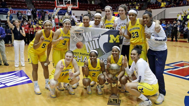 Michigan players pose with the trophy after winning the WNIT championship over Georgia Tech, 89-79, in 3 OTs on April 1, 2017 at Calihan Hall in Detroit.