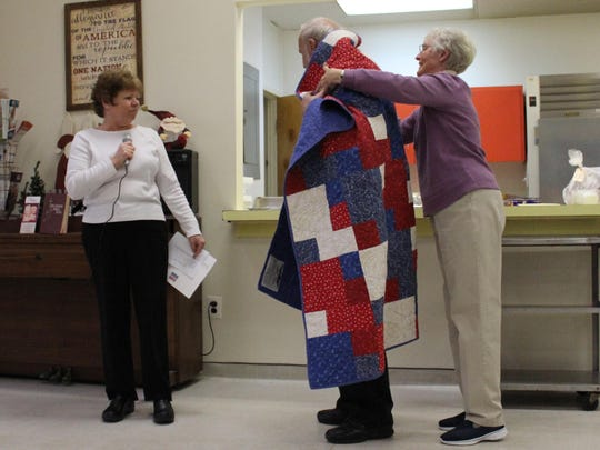 Charles Dalley is presented with his quilt by members of the Quilts of Valor Foundation.