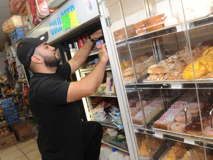 """Fabian Hernandez, general manager of Abarrotes Sin Limite grocery store, stocks  items next to Mexican bakery cookies and breads Sept. 24, 2014. The Lincoln Park store, whose name translates to """"groceries without limits,"""" is part of Lincoln Park's thriving Mexican community."""